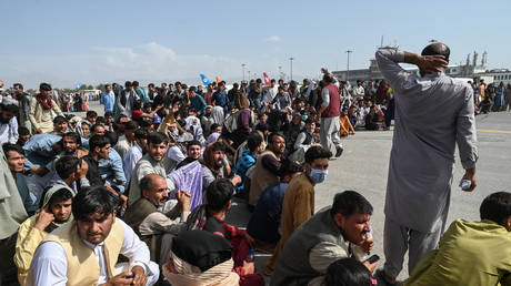 Afghan passengers sit as they wait to leave the Kabul airport in Kabul on August 16, 2021, after a stunningly swift end to Afghanistan's 20-year war, as thousands of people mobbed the city's airport trying to flee the group's feared hardline brand of Islamist rule. © Wakil Kohsar / AFP