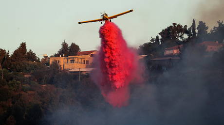 A firefighting plane disperses fire retardant near the Israeli village of Beit Meir on the outskirts of Jerusalem on August 16, 2021.
