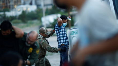 FILE PHOTO: A migrant from Central America is searched by a US Border Patrol agent after crossing into the United States from Mexico, in Sunland Park, New Mexico, July 22, 2021.