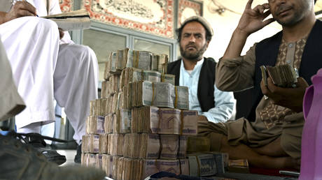 Currency dealers count Afghani banknotes at the Shahzada exchange market in Kabul on June 21, 2021.