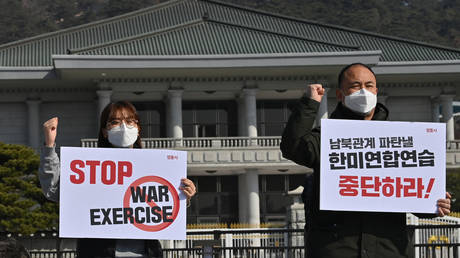 """FILE PHOTO. Anti-war activists hold placards reading """"Stop war exercise!"""" during a protest against a joint military drill between South Korea and the United States in Seoul. © AFP / Jung Yeon-je"""