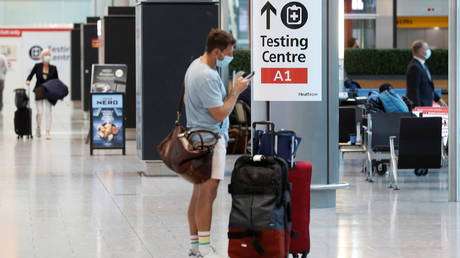 FILE PHOTO. A passenger stands next to a COVID-19 testing centre sign in the International arrivals area of Terminal 5 in London's Heathrow Airport, Britain, August 2, 2021. © Reuters / Peter Nicholls