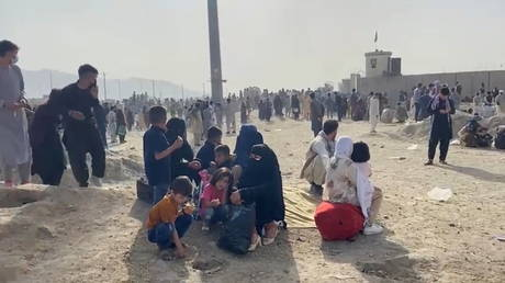 People gathered outside the Hamid Karzai International Airport react to gunfire as US troops oversee an evacuation effort, in Kabul, Afghanistan, August 18, 2021.