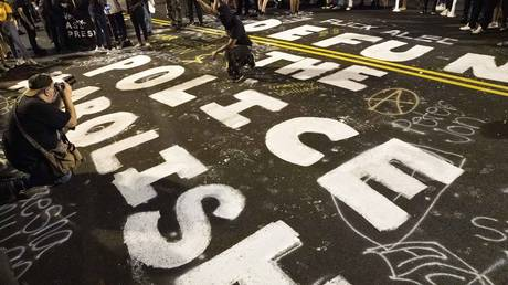 FILE PHOTO. Demonstrators raise their fists around a mural dedicated to defund and abolish the police, during a rally to protest US President Donald Trump's acceptance of the Republican National Convention nomination at Black Lives Matter plaza in Washington, DC. © AFP / Jose Luis Magana