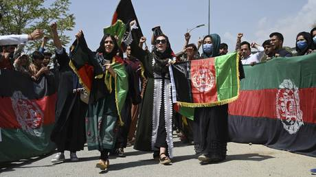 Afghans celebrate the 102th Independence Day of Afghanistan with the national flag in Kabul on August 19, 2021. © AFP / WAKIL KOHSAR