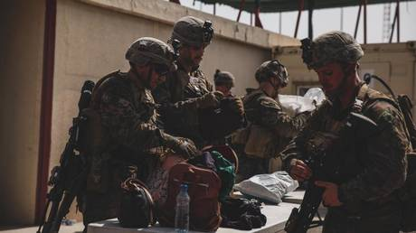 Marines with the 24th Marine Expeditionary Unit (MEU) search luggage during an evacuation at Hamid Karzai International Airport, Kabul, Afghanistan, August 18, 2021