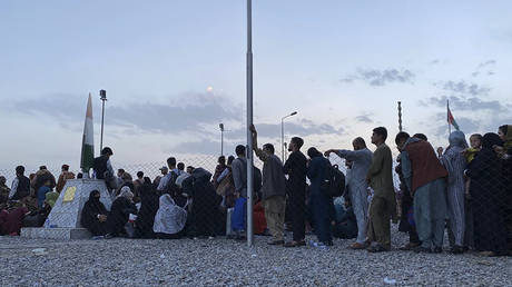 Afghans queue up to board an aircraft to leave Afghanistan at the military airport in Kabul. © AFP / Shakib Rahmani