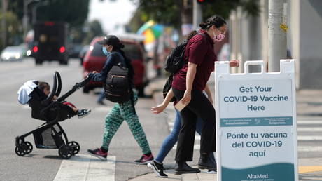 People walk past a sign for a coronavirus disease (COVID-19) vaccination clinic in Los Angeles, California