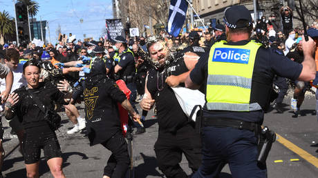 Police pepper spray protesters during an anti-lockdown rally in Melbourne on August 21, 2021.