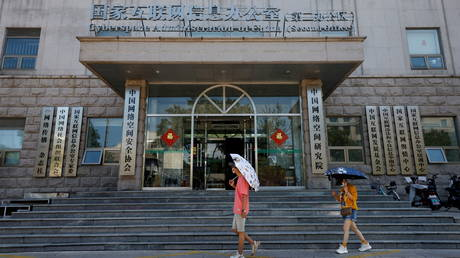 FILE PHOTO: People walk past an office of the Cyberspace Administration of China (CAC) in Beijing, China, July 8, 2021.