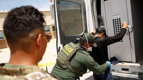 A US Border Patrol is shown in July detaining a migrant in New Mexico.