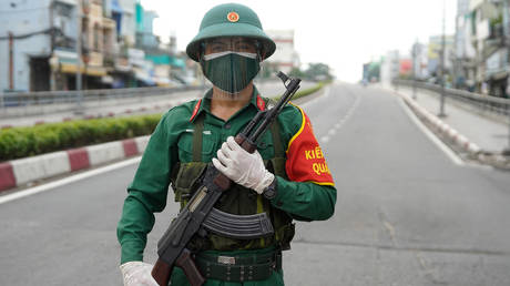 A Vietnamese military personnel stands guard on a deserted road in Ho Chi Minh City on August 23, 2021, after the government imposed a stricter lockdown until September 16 to stop the spread of the COVID-19 coronavirus. © AFP / Pham THO