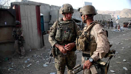British soldier (L) and a member of the US Armed Forcesin conversation while working at Kabul Airport on August 22, 2021.© AFP / MOD