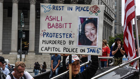 FILE PHOTO. A right wing protester holds a sign about Ashli Babbitt while participating in a political rally on July 25, 2021 in New York City. © Getty Images / Stephanie Keith