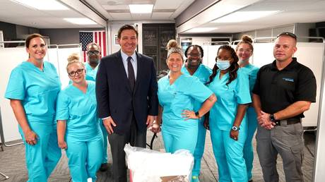 Florida Gov. Ron DeSantis (center) poses with medical staff contracted to distribute monoclonal antibody treatments, Jacksonville, August 12, 2021.
