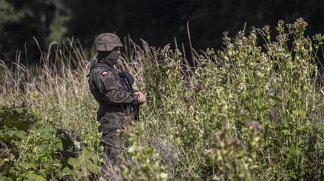 A Polish border guard stands near the border with Belarus, on August 20, 2021. © AFP / Wojtek RADWANSKI
