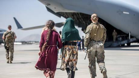 A US Marine walks with children during an evacuation at Hamid Karzai International Airport in Kabul, Afghanistan, August 24, 2021 © Reuters / US Marine Corps / Sgt. Samuel Ruiz