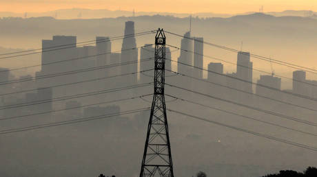 The downtown Los Angeles skyline is seen behind an electricity pylon at sunrise in Los Angeles, California, US