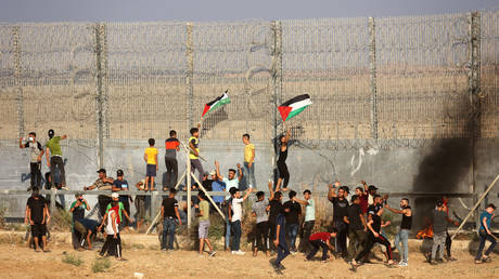 Palestinian protesters lifting national flags burn tyres during a demonstration by the border fence with Israel, east of Gaza City, denouncing the Israeli siege of the Palestinian strip, on August 21, 2021.© AFP / SAID KHATIB