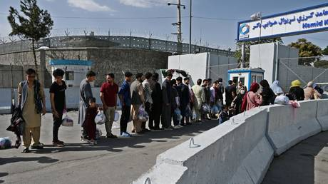Afghans, hoping to leave Afghanistan, queue at the main entrance gate of Kabul airport in Kabul on August 28, 2021