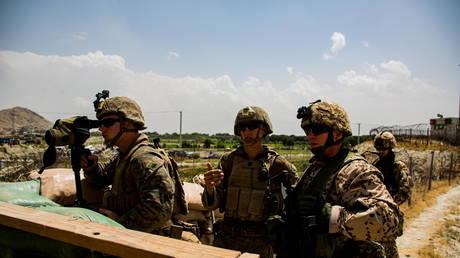 U.S. Marines and German service member watch an entry gate during an evacuation at Hamid Karzai International Airport, Kabul, Afghanistan, August 28, 2021. © Reuters/U.S. Marine Corps/Cpl. Davis Harris