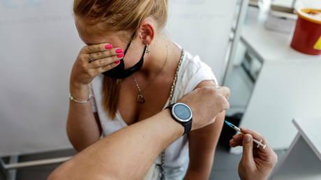An Israeli woman receives a third shot of coronavirus vaccine in Tel Aviv. © Reuters / Amir Cohen