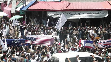 Crowd carries makeshift coffins draped in NATO, US and UK flags during a pretend funeral on a street in Khost, Afghanistan August 31, 2021.