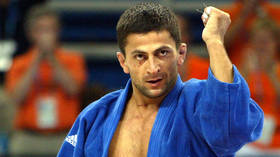 Olympic judo champ 'attends brother's funeral with cops' while 'facing premeditated murder charges from shootout that killed him'