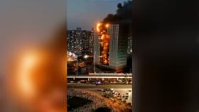 Fire tears through Chinese skyscraper as debris falls onto streets below (VIDEO)