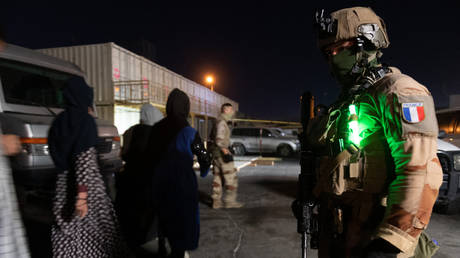 A French soldier watching people walking to board a A400M Atlas military transport aircraft at Kabul airport, Afghanistan on August 24, 2021.