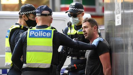 Police arrest a protester during an anti-lockdown rally in Melbourne on August 21, 2021 as the city experiences its sixth lockdown