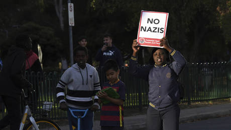 A boy carries a placard during a demonstration in Melbourne, Dec. 4, 2017 ©James Ross AAP / Image via AP