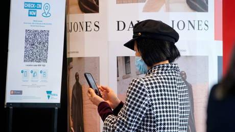 A woman scans a QR code to enter a store in Melbourne, Victoria, Australia, June 11, 2021 © Reuters / Sandra Sanders