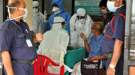 FILE PHOTO: Medics wearing protective gear examine a patient at a hospital in Kozhikode in the southern state of Kerala, India, May 21, 2018.