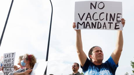 An activist raises a sign to protest against Covid vaccine mandates during a demonstration in Akron, Ohio, August 16, 2021.