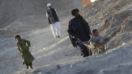 FILE PHOTO: An internally displaced Afghan boy sits in a handcart pushed by his father at a refugee camp in Kabul, Afghanistan.