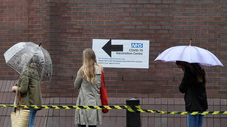 People queue in the rain to receive a COVID-19 vaccination amid the spread of the coronavirus disease pandemic, London