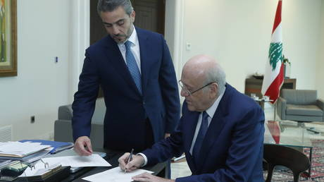 Lebanon's Prime Minister Najib Mikati signs a decree for the formation of the new Lebanese government at the presidential palace in Baabda. © Reuters / Dalati Nohra
