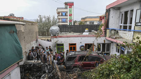 Afghan residents and family members of the victims gather next to a damaged vehicle inside a house, day after a US drone airstrike in Kabul on August 30, 2021. © AFP/WAKIL KOHSAR