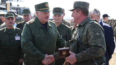 FILE PHOTO: Belarusian President Alexander Lukashenko greets Russian army officer during the military exercise Zapad-2021in Belarus, on September 12, 2021.