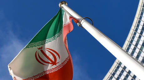 The Iranian national flag is seen outside the International Atomic Energy Agency (IAEA) headquarters during the agency's Board of Governors meeting in Vienna on March 1, 2021. © AFP / Joe Klamar
