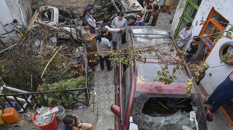 Afghan residents and family members of the victims gather next to a damaged vehicle inside a house, day after a US drone airstrike in Kabul on August 30, 2021