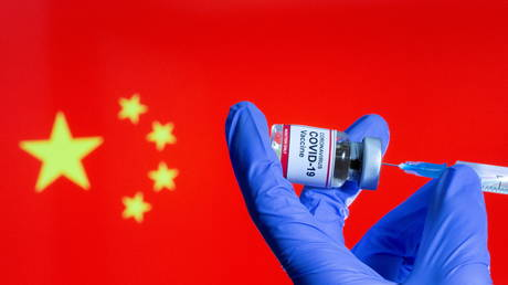 """A woman holds a small bottle labeled with a """"Coronavirus COVID-19 Vaccine"""" sticker and a medical syringe in front of displayed China flag © Reuters / Dado Ruvic"""