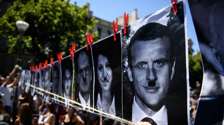 Protestors show a banner depicting faces of politicians, including President Macron, with Hitler's moustache during a demonstration against the new coronavirus safety measures in Marseille on July 17, 2021. © AFP / Clement Mahoudeau