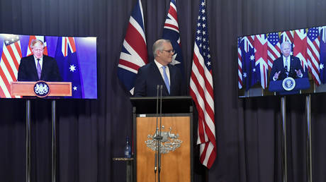 Australia's Prime Minister Scott Morrison appears on stage with video links to Britain's Prime Minister Boris Johnson and U.S. President Joe Biden at a joint press conference
