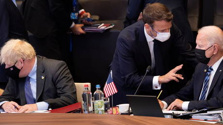 FILE PHOTO: French President Emmanuel Macron talks with US President Joe Biden before a plenary session at a NATO summit in Brussels, Belgium on June 14, 2021