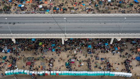 Migrants take shelter near the Del Rio International Bridge in Del Rio, Texas