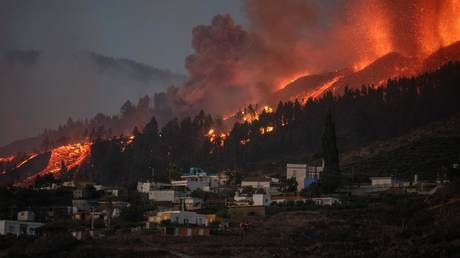 A river of lava approaches houses as Mount Cumbre Vieja erupts in El Paso, spewing out columns of smoke, ash and lava as seen from Los Llanos de Aridane on the Canary island of La Palma on September 19, 2021. © DESIREE MARTIN / AFP