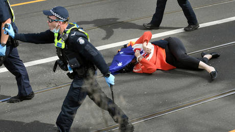 A protester is pushed to the ground by the police during an anti-lockdown rally in Melbourne on September 18, 2021