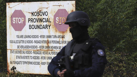 A Kosovo special police officer stands on the road near the Jarinje checkpoint with Serbia, September 20, 2021.